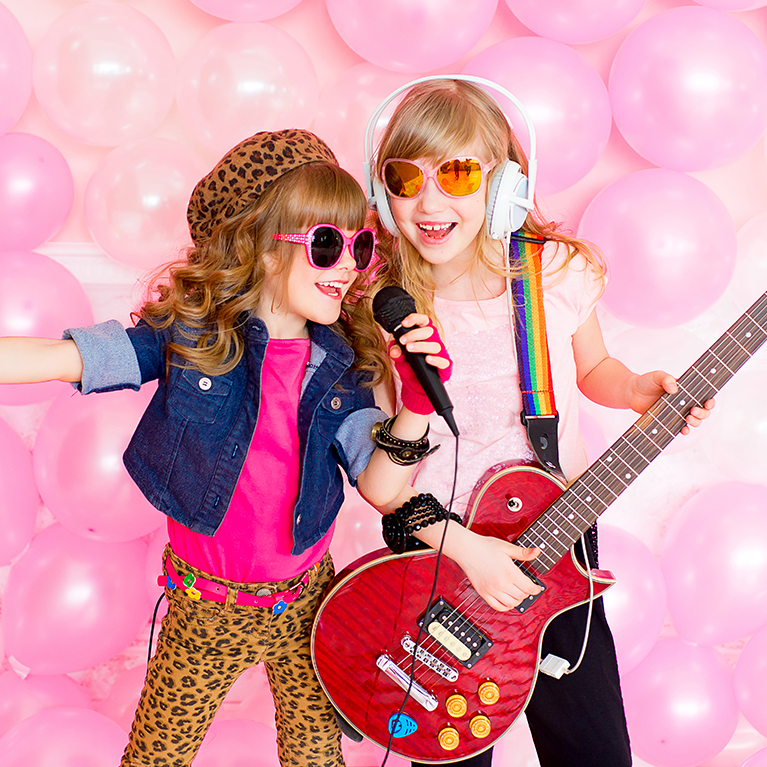 two-little-girl-singing-a-song-with-a-microphone-and-a-guitar-on-a-background-of-pink-balloons-thorne-travel-kilwinning-406262368
